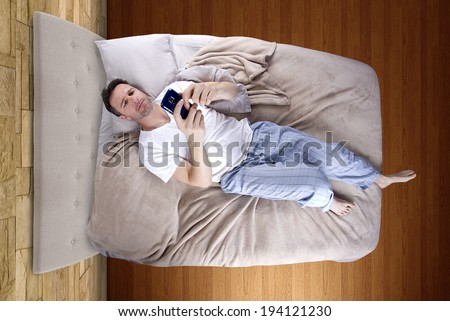 man snoozing modern cell phone alarm clock - stock photo
