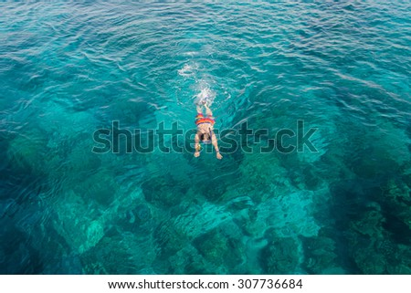 Man snorkeling over coral reef with clear blue ocean water, top view - stock photo