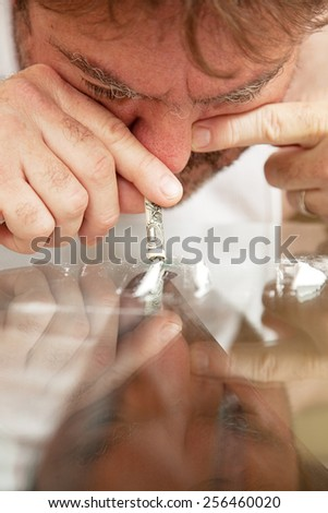 Man snorting cocaine off of his glass coffee table with a rolled up dollar bill.    - stock photo
