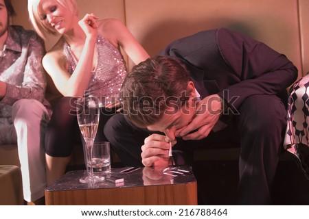 Man snorting drugs at a nightclub. - stock photo