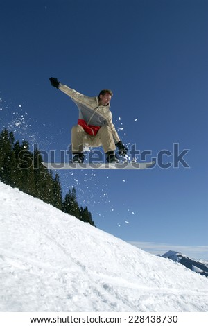 Man snowboarding, jumping in the air