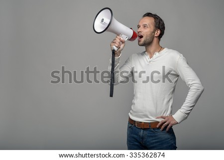 Man speaking over a megaphone as he makes a public address, participates in a protest or organises a rally or promotion, over grey with copy space to the side