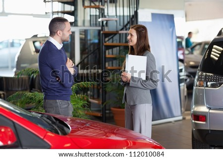 Man speaking with a businesswoman in a dealership - stock photo