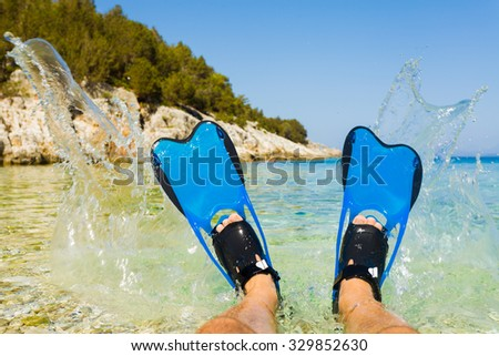 Man splashing with his lags equipped with snorkeling flippers. - stock photo