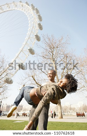 Man spontaneously carrying girlfriend in his arms while visiting London city, with the London Eye and a blue sky in the background. - stock photo