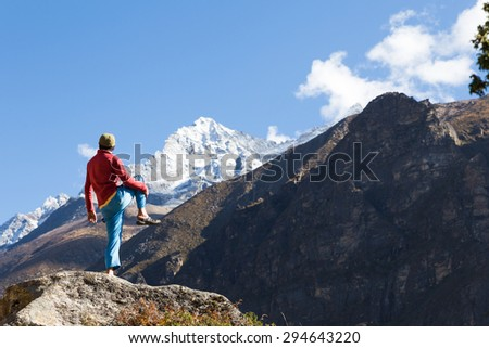 Man sportsman rear view standing one leg on stone, practicing yoga asana in front snow peaks mountains. Everest Base Camp trail route traveling, Himalaya range tourism.