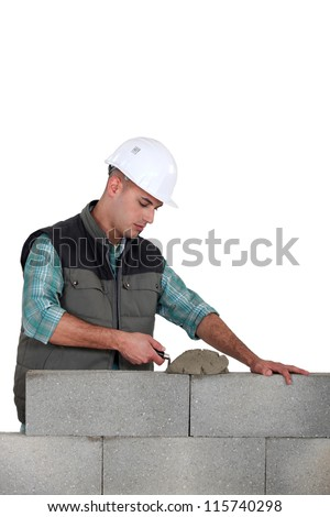 Man spreading mortar with a trowel - stock photo