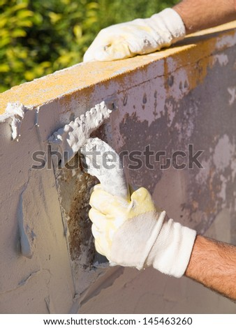 Man spreading tile adhesive on a wall in a sunny day.