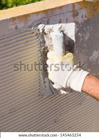 Man spreading tile adhesive with a trowel in a sunny day. - stock photo