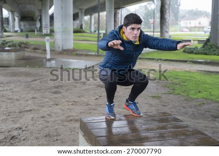 Man squatting in a park on a rainy day - stock photo