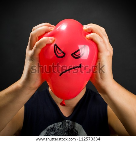Man squeezing red balloon with angry smiley - stock photo