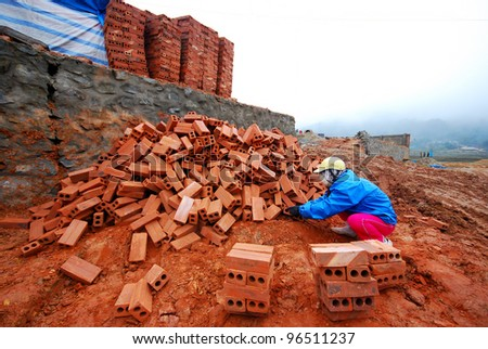 Man stack up bricks at construction site during winter cold weather - stock photo