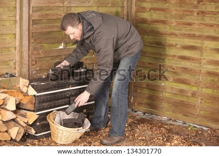 man stacking coal briquette for burning stove (chimney).