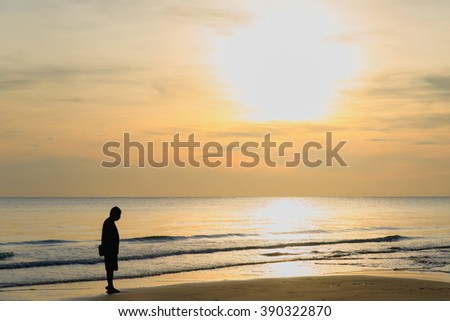 Man stand alone on the beach at sunset. Calm sea with waves.