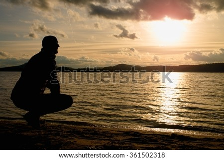 Man stand near beach look to sunset,  peaceful water level