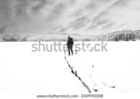 Man stand on wooden bridge in winter mountains, high key black and white winter landscape  - stock photo