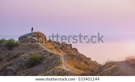 Man standing alone on the edge of Meganom Cape. Stunning landscape of Meganom cape on sunset. Travel Crimea, Russia