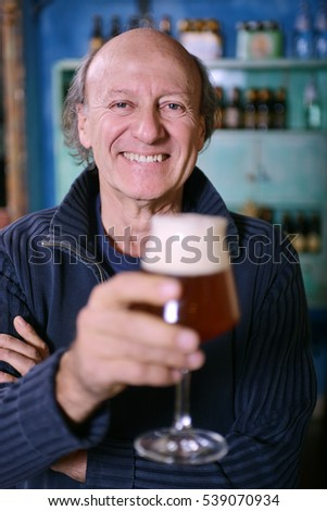 Man standing and holding a glass of beer