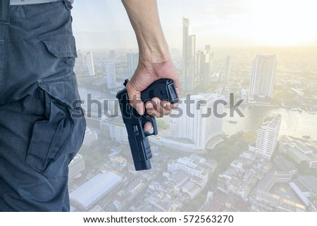 man standing and holding a gun, pistol with city background