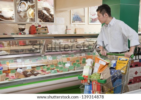 Man standing and looking at the Deli counter, Beijing - stock photo