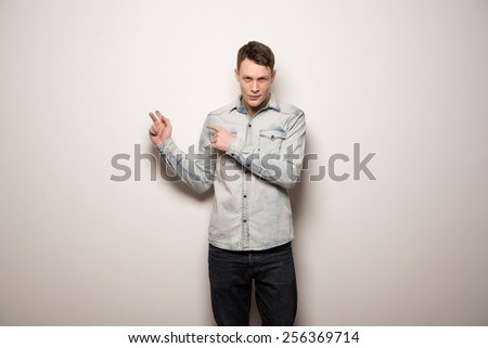 man standing and presenting over empty white wall background - stock photo