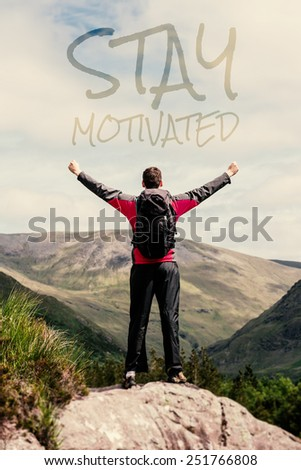 Man standing at hill top cheering against stay motivated - stock photo