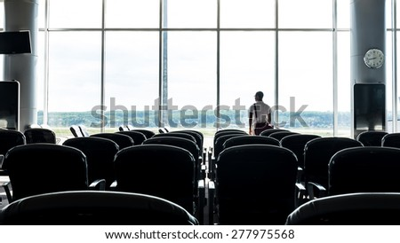 Man standing at the window lounge terminal of the airport Waiting for flight - stock photo