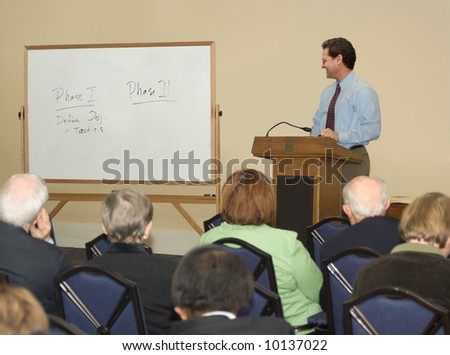 Man standing behind a podium, looking at a whiteboard before a group of adults - stock photo