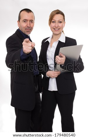 Man standing beside a woman and pointing at the camera - stock photo