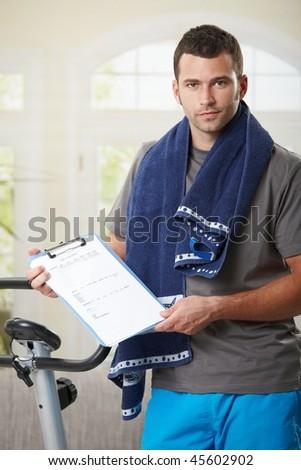 Man standing beside stationary bike showing training plan. - stock photo