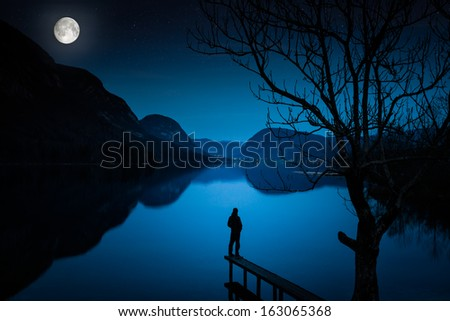 Man Standing by Lake, Covered with Moonlight Moonlight, Thinking Man standing on the pier - stock photo