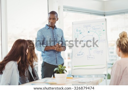 Man standing by white board while discussing with coworkers at office - stock photo