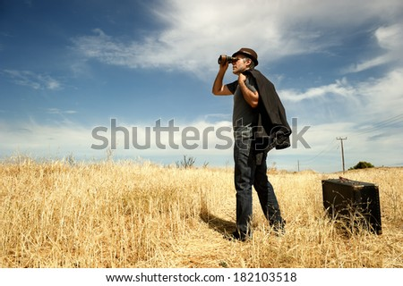 Man standing in a field watching with binoculars  - stock photo