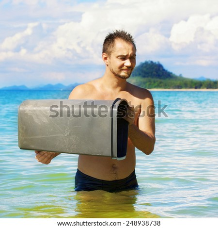 man standing in a sea with trashcan in his hands - stock photo