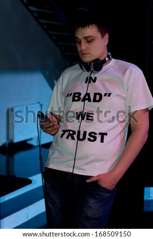 Man standing in darkness listening to music on his storage device through a set of headphones as he leans against a pole - stock photo