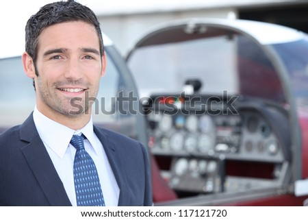 man standing in front of a plane cockpit - stock photo