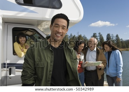 Man standing in front of RV at lake with family behind - stock photo