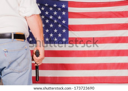 man standing in front of the stars and stripes holding a handgun - stock photo