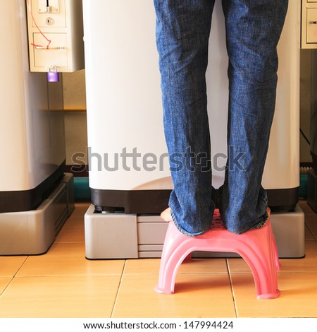 Man standing in front of washing machines coin - stock photo