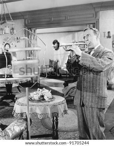 Man standing in his living room playing the trumpet to a bird - stock photo