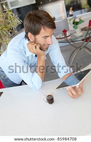 Man standing in kitchen with electronic tablet