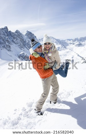 Man standing in snow lifting girlfriend with mountain in background - stock photo