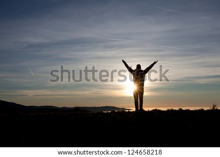 man standing in sunset on mountain