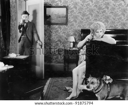 Man standing in the doorway looking at a woman angry at her dog