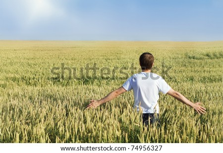 Man standing in wheat field with arms outstretched