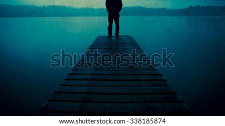 Man Standing Jetty Tranquil Lake Gloomy Fog Dusk Concept - stock photo