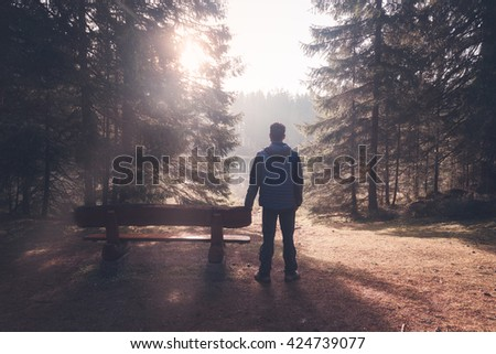 Man standing near bench at sunny morning forest