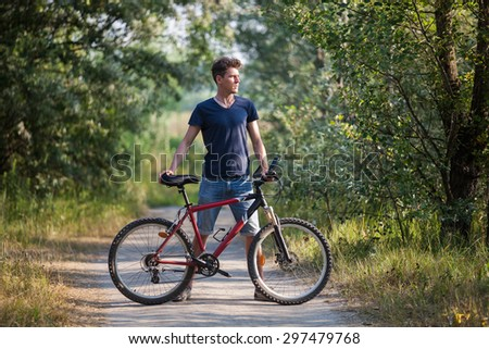 Man standing near bicycle in the park - stock photo