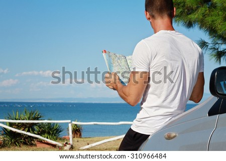 Man standing near the car and looking at road map. Traveler searching right direction on map. Tourism, active lifestyle concept - stock photo
