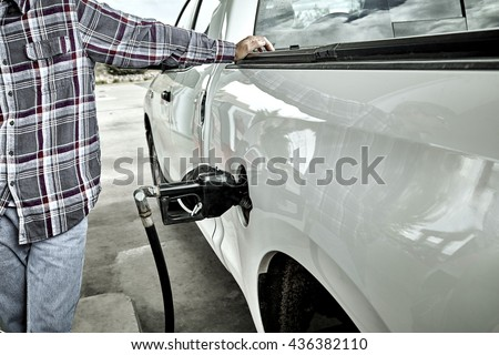Man standing next to pick up truck pumping gas - stock photo